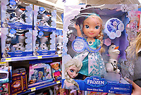STAFF PHOTO BEN GOFF  @NWABenGoff -- 12/16/14 A Walmart associate displays a Snow Glow Elsa doll from Disney's 'Frozen' movie, with a variety of other 'Frozen' toys in the background, at the Walmart Supercenter on Pleasant Crossing Boulevard in Rogers on Tuesday Dec. 16, 2014. The toy was one of the top 20 picked by children through Walmart's Chosen by Kids program and has been a top selling toy in stores.