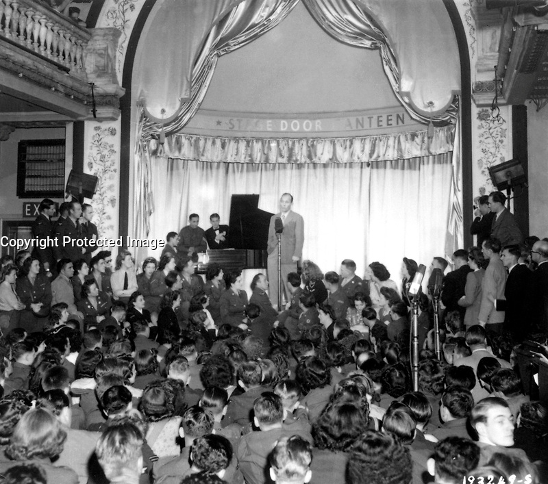 Bing Crosby, stage, screen and radio star, sings to Allied troops at the opening of the London stage door canteen in Piccadilly, London, England.  August 31, 1944. Pearson. (Army)<br /> NARA FILE #:  111-SC-193249<br /> WAR &amp; CONFLICT #:  904
