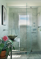 The contemporary shower room is decorated with pale grey tiles and has a round chrome basin