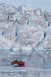 Tourist boat in front of large iceberg at midnight, end of June, mid summer night; Disko Bay, Greenland