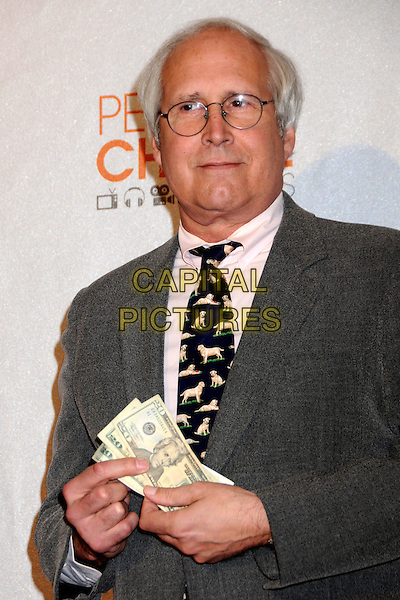CHEVY CHASE.Pressroom at the 36th Annual People's Choice Awards held at the Nokia Theatre LA Live, Los Angeles, California, USA..January 6th, 2009.press room half length grey gray suit jacket pink shirt dog print tie black glasses money cash dollars.CAP/ADM/BP.©Byron Purvis/AdMedia/Capital Pictures.