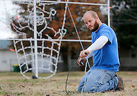 NWA Democrat-Gazette/DAVID GOTTSCHALK  Dustin Davis, a maintenance two worker with the city of Springdale Parks and Recreation Department, strings an extension cord Wednesday, November 25, 2015, from the Hot Air Balloon light display in downtown Springdale. The holiday decoration is one that is being relocated from Murphy Park to areas of downtown Springdale because of work taking place in the park.