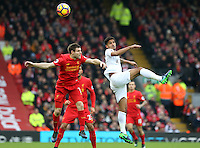 Kyle Naughton of Swansea City beats James Milner (vice-captain) of Liverpool to the aerial ball during the Premier League match between Liverpool and Swansea City at Anfield, Liverpool, Merseyside, England, UK. Saturday 21 January 2017