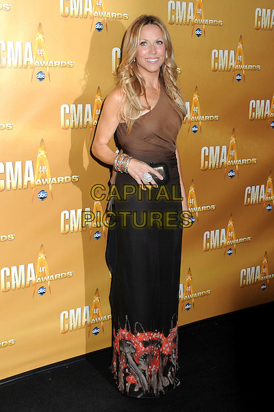 SHERYL CROW .44th Annual CMA Awards, Country Music's Biggest Night, held at Bridgestone Arena, Nashville, Tennessee, USA, 10th November 2010..CMAs country music full length one shoulder brown  ombre dress long maxi red print hand clutch bag bracelet .CAP/ADM/LF.©Laura Farr/AdMedia/Capital Pictures.