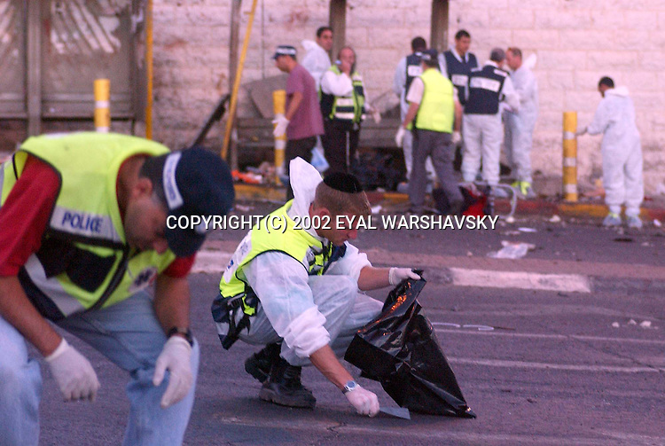 Rescue workers and police forensic volunteers search the site of a suicide bombing in Jerusalem Wednesday June 19 2002. A suicide bomber exploded at a bus station wednesday killing seven and wounding 40 Photo by Eyal Warshavsky