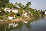 Pretty houses line the banks of river at Helford village, Cornwall, England