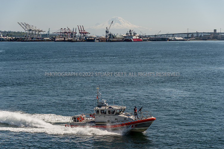 4/9/2016-- Seattle, WA, USA<br /> <br /> A US Coast Guard speed boat patrols Puget Sound near Seattle, following a Washington State frry to Bainbridge Island.<br /> <br /> <br /> <br /> Photograph by Stuart Isett. &copy;2016 Stuart Isett. All rights reserved.