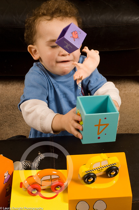 2 year old toddler boy at home playing with toys experimenting using block to toss toy pig and smaller block into the air vertical