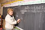 K-8 Parochial School Bronx New York Grade 3 female teacher working on blackboard mathematics lesson on measurement horizontal