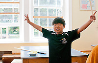Exuberant lad at lunchtime, Summerhill School, Leiston, Suffolk. The school was founded by A.S.Neill in 1921 and is run on democratic lines with each person, adult or child, having an equal say.  You don't have to go to lessons if you don't want to but could play all day.  It gets above average GCSE exam results.