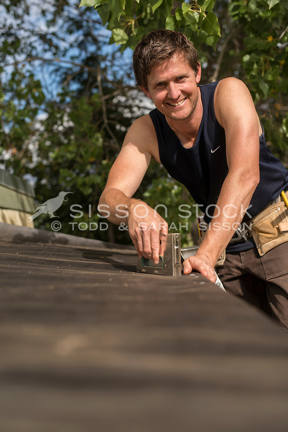 Home handyman Home handyman stapling building paper to a roof while working outside on a home renovation project, New Zealand- stock photo, canvas, fine art print