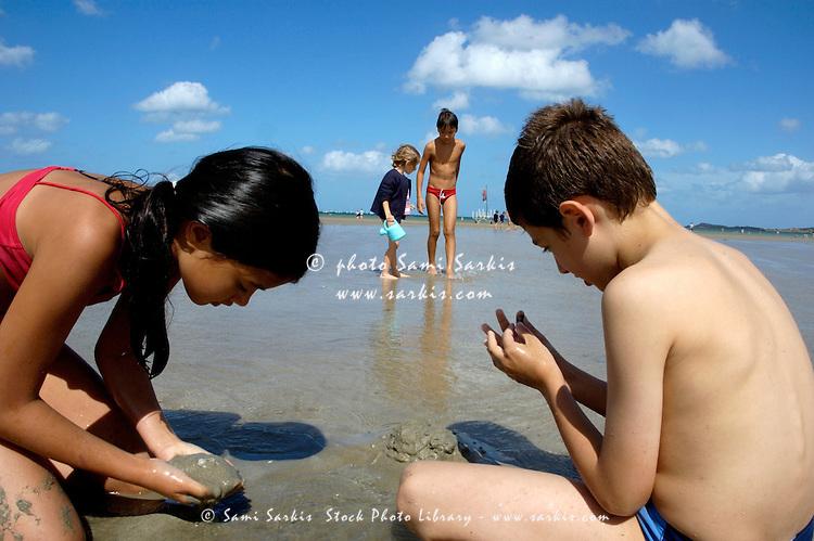 Two children digging in the wet sand at Penguen Beach, Saint-Cast-le-Guildo, France.