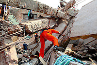 Rescue workers look for survivors in the collapsed wreckage of the Rana Plaza complex in Savar. The 8 storey building, which housed a number of garment factories employing over 3,000 workers, collapsed on 24 April 2013. By 29 April, at least 380 were known to have died while hundreds remained missing. Workers who were worried about going to work in the building when they noticed cracks in the walls were told not to worry by the building's owner, Mohammed Sohel Rana, who is a member of the ruling Awami League's youth front. He fled his home and tried to escape to neighbouring India after the building collapsed but was caught by police and brought back to Dhaka. Some of the factories working in the Rana Plaza building produce cheap clothes for various European retailers including Primark in the UK and Mango, a Spanish label. . /Felix Features