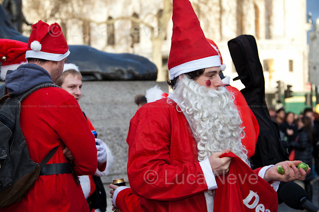 "London, 15/12/2012. Hundreds of people dressed as Santa Claus and similar other outfits gathered in Trafalgar square to celebrate the annual event called ""Santacon"". After a funny battle fought using Brussels sprouts, around 6 PM, one of the Santas climbed the 20 meters Christmas tree. When he came down he was held for a while by the Heritage Wardens but at the end he managed to escape throughout the crowd."