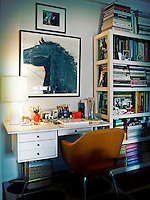 A retro style chair at a white desk with a lit lamp a laptop and other office items. Next to it, books and folders are neatly stored in an open shelving unit.