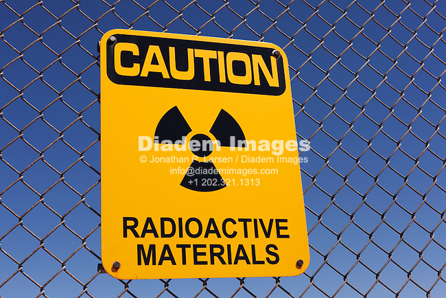 A radioactive materials sign on a fence.