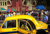 Commuters walk past a taxi parked outside the Howrah Junction railway station in Kolkata, India, on Friday, May 26, 2017.  Photographer: Sanjit Das