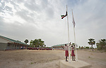 Two students unfurl the national flag at the beginning of the day in the Loreto Primary School in Rumbek, South Sudan. The Loreto Sisters began a secondary school for girls in 2008, with students from throughout the country, but soon after added a primary in response to local community demands.