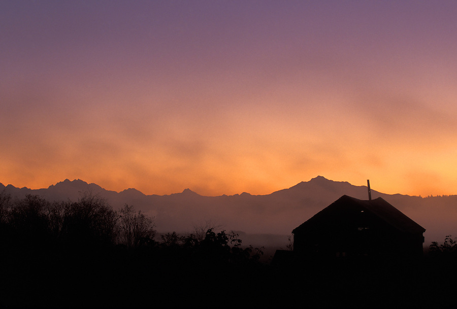Barn silhouetted against sunrise, Cascade Mountains in background, Spencer Island, Everett, Snohomish River Estuary, Washington