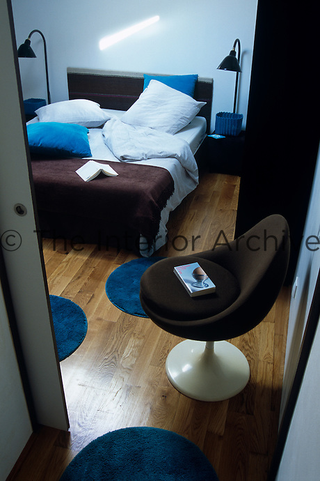 Small circular blue rugs appear as stepping stones on the wooden floor of this modern chocolate and blue schemed contemporary bedroom