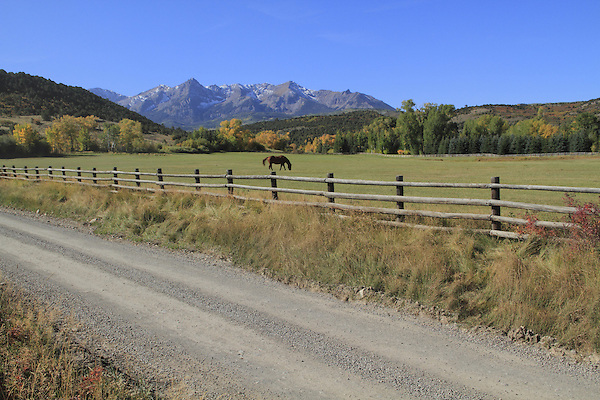 Dirt road with the Sneffels Range in the San Juan Mountains, autumn, Colorado.