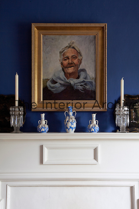 A pair of glittering candlesticks and vases flank the portrait hanging over the fireplace in the dining room