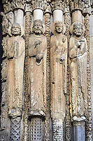 .West Facade, central Portal c. 1145,  Cathedral of Notre Dame, Chartres, France. Gothic statues of four elongated human figures with halos. The leftmost is a bearded man holding a book. The next is a crowned man with long hair and a beard also holding a book. The next is a crowned female with elaborate garments. The rightmost is a bearded, crowned man holding a scroll. Some scholars believe that the jamb figures are the ancestors of Christ.. A UNESCO World Heritage Site. .