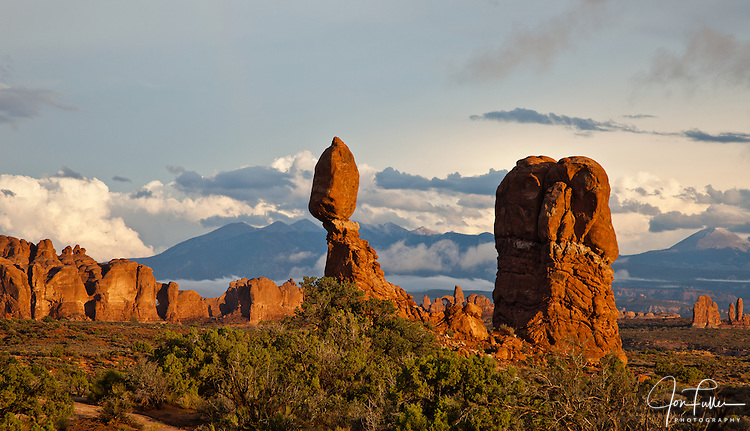 Balanced Rock at sunset with clearing storm clouds in Arches National Park, Moab, Utah, USA and the La Sal Mountains in the background.