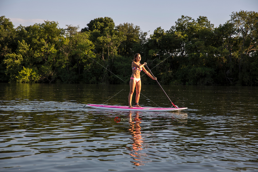 Attractive young female woman getting exercise by paddle boarding on Lady Bird Lake, downtown Austin, TX