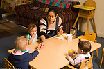 Day Care Center female caregiver at table with babies eating morning snack, giving toddler grated apple