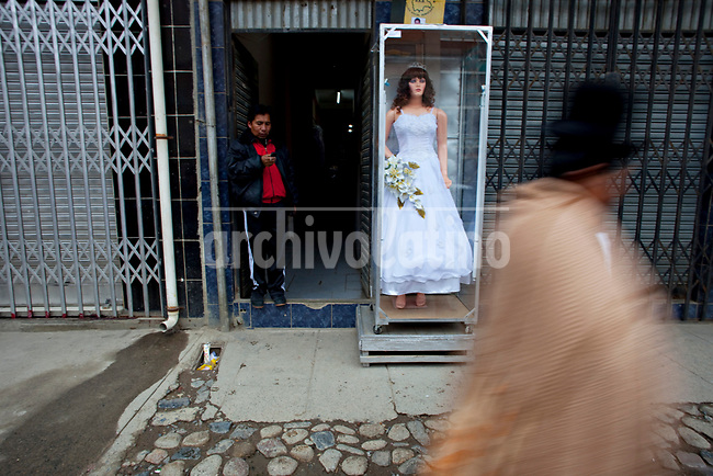 .An Ayamara woman walks pass by a wedding dresses store in El Alto..Just 25 years ago it was a small group of houses around La Paz  airport, at an altitude of 12,000 feet. Now El Alto city  has  nearly one million people, surpassing even the capital of Bolivia, and it is the city of Latin America that grew faster ...It is also a paradigmatic city of the tubles and traumas of the country. There got refugee thousands of miners that lost  their jobs in 90 ¥s after the privatization and closure of many mines. The peasants expelled by the lack of land or low prices for their production. Also many who did not want to live in regions where coca  growers and the Army  faced with violence...In short, anyone who did not have anything at all and was looking for a place to survive ended up in El Alto...Today is an amazing city. Not only for its size. Also by showing how its inhabitants,the poorest of the poor in one of the poorest countries in Latin America, managed to get into society, to get some economic development, to replace their firs  cardboard houses with  new ones made with bricks ,  to trace its streets,  to raise their clubs, churches and schools for their children.