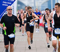 08 AUG 2010 - LONDON, GBR - Formula 1 Grand Prix driver Jenson Button checks his run lap times during the 2010 Challenger World London Triathlon age group race (PHOTO (C) NIGEL FARROW)