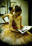 Ballerina in a tutu reading a magazine backstage