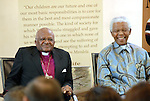 "Archbishop Desmond Tutu and Nelson Mandela, pictured in front of a quote by Mandela saying: ""Our children are our future and one of our most basic responsibilities is to care for them in the best and most compassionate manner possible."""