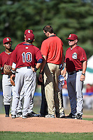 Mahoning Valley Scrappers pitching coach Greg Hibbard (37) looks on as the trainer talks with pitcher Edward Estrella (49) as Juan De La Cruz (back) and Yonathan Mendoza (10) listen in during a game against the Jamestown Jammers on June 15, 2014 at Russell Diethrick Park in Jamestown, New York.  Jamestown defeated Mahoning Valley 9-4.  (Mike Janes/Four Seam Images)