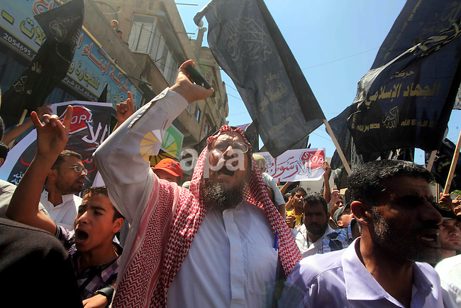 Palestinians hold placards as they shout anti-U.S. slogans during a demonstration against the controversial film 'Innocence of Muslims' in Khan Younis southern Gaza strip, on September 14, 2012. The controversial low budget film reportedly made by an Israeli-American which portrays Muslims as immoral and gratuitous, sparked fury in Libya, where four Americans including the ambassador were killed on Tuesday when a mob attacked the US consulate in Benghazi, and has led to protests outside US missions in Morocco, Sudan, Egypt, Tunisia and Yemen. Photo by Ashraf Amra