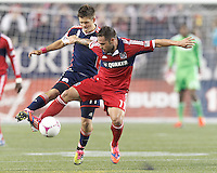 New England Revolution midfielder Kelyn Rowe (11) and Chicago Fire midfielder Daniel Paladini (11) battle for the ball. In a Major League Soccer (MLS) match, the New England Revolution (blue) defeated Chicago Fire (red), 1-0, at Gillette Stadium on October 20, 2012.