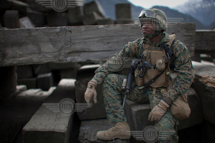 A marine rests in a lumber yard whilst on a mission in Nishigham village in Nuristan. They have recently disrupted the illegal logging trade that smuggles wood across the border from Afghanistan causing some hostility in the area from local smugglers and gangsters. The mission was a joint patrol with the marines to the nearby village of Nishigham to re-supply an OP (Observation Post) that had been attacked the day before killing one ANA (Afghan National Army) soldier. The marines are acting as an ETT (Embedded Training Team) to mentor the ANA with the ultimate aim of leaving the country's security for the local Army to deal with.