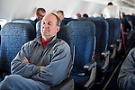 coach rests in the front of the plane en route to Ann Arbor
