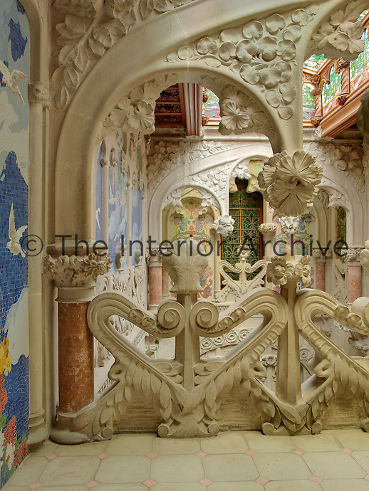 A view through one of the ornately carved arches of the staircase gallery. A blue mosaic sky with flying birds forms one of several decorative panels across the wall