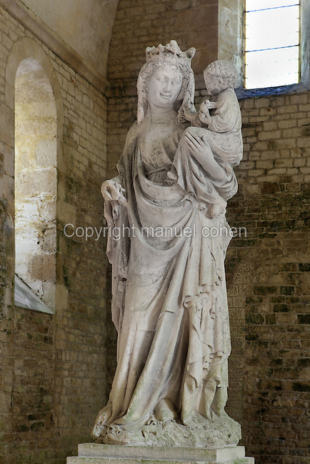 Statue of Our Lady of Fontenay, Fontenay Abbey, Marmagne, Cote d'Or, France. This Cistercian abbey was founded by Saint Bernard of Clairvaux in 1119, built in the Romanesque style. The abbey itself housed 300 monks from 1200, but was sacked during the French Revolution. The statue of Fontenay's Virgin Mary is in the northen transept arm of the abbey church. It dates from the late 13th century and is an example of Burgundian statuary. Mary carries Jesus in her left arm and her right hand originally held a sceptre. Her smile is typical of statues from the Champagne region, while her stance, with her weight on one hip, and the marked folds in her clothes are more typical of the Burgundian tradition. Picture by Manuel Cohen