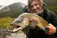 An angler holds a New Zealand brown trout caught on the South Island.
