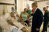 Washington, D.C. - July 1, 2005 -- United States President George W. Bush shares a light moment with Sergeant John Iverson and his wife, Pamela, during the President's visit Friday, July 1, 2005, to Walter Reed Army Medical Center.  The Long Beach, California soldier is recovering from injuries sustained while serving in Operation Iraqi Freedom.  <br /> Credit: Eric Draper - White House via CNP