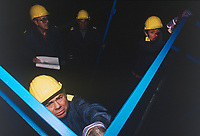 Switzerland. Canton Lucerne. A group of men with yellow helmets build bunk beds in the Sonnenberg tunnel in Lucerne during the largest civil defense exercise ever held in the country. From 16 to 21 November 1987, almost 1200 men and women converted a motorway tunnel into perhaps the world's largest bunker structure. The civil protectors had to prove during the exercise «Ameise» ( Ants in english) that in an emergency more than 20,000 inhabitants of the city of Lucerne could survive here in the mountain for two weeks. The Sonnenberg Tunnel is a 1,550m  long motorway tunnel, constructed between 1971 and 1976. At its completion it was also the world's largest civilian nuclear fallout shelter, designed to protect 20,000 civilians in the eventuality of war or disaster. Based on a federal law from 1963, Switzerland aims to provide nuclear fallout shelters for the entire population of the country. The construction of a new tunnel near an urban centre was seen as an opportunity to provide shelter space for a large number of people at the same time. The giant bunker was built between 1970 and 1976 at a cost of 40 million Swiss francs. The shelter consisted of the two motorway tunnels (one per direction of travel), each capable of holding 10,000 people in 64 person subdivisions. A seven story cavern between the tunnels contained shelter infrastructure including a command post, an emergency hospital, a radio studio, a telephone centre, prison cells and ventilation machines. The shelter was designed to withstand the blast from a 1 megaton nuclear explosion 1 kilometer away. The blast doors at the tunnel portals are 1.5 meters thick and weigh 350 tons. The logistical problems of maintaining a population of 20,000 in close confines were not thoroughly explored, and testing the installation was difficult because it required closing the motorway and rerouting the usual traffic. The only large-scale test, a five-day exercise in 1987 to practice converting the road tunnels into