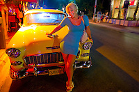 An admiring woman leans up against a 1955 Chevy Bel Air along the neon-soaked Ocean Drive in Miami's South Beach.