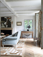 In the elegant family sitting room, the custom-made sofas are covered in pale blue Donghia mohair; a painting by Santiago Castillo hangs above an 18th-century French limestone fireplace, the abaca rug is by Patterson Flynn Martin and the curtains are a linen fabric by Chelsea Textiles. The x-frame stool is by Maison Jansen.