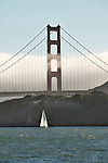 Golden Gate Bridge with a passing sail boat in San Francisco, California at sunset