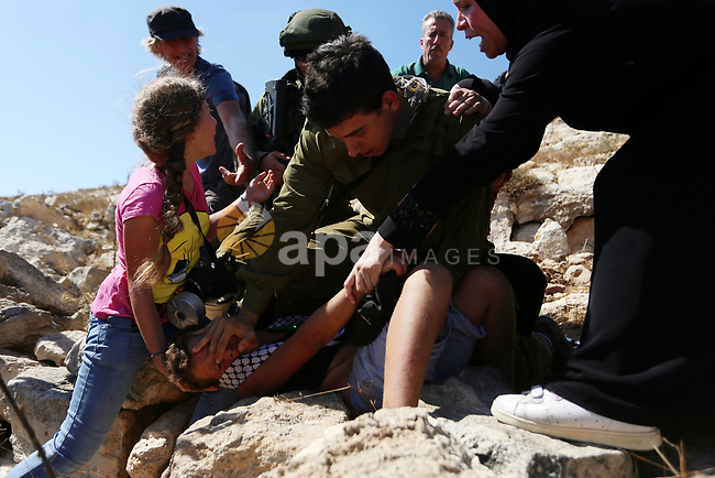 (FILES) This file photo taken on August 28, 2015 shows Palestinian Ahed Tamimi (L) fighting with other members of her family to free a Palestinian boy (bottom) held by an Israeli soldier (C) during clashes between Israeli security forces and Palestinian protesterson in the West Bank village of Nabi Saleh near Ramallah. Israel's army arrested Ahed Tamimi on December 19, 2017, after a video went viral of her slapping Israeli soldiers in the occupied West Bank as they remained impassive. Photo by Shadi Hatem
