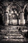 Large pillars supporting gothic arches in abbey ruins in England