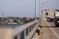 Morehead City, NC -- Quadriplegic hand cyclist Paul Kelly, 62, descends the bridge to Atlantic Beach over the intercostal waterway on a training ride for the Boston Marathon Tuesday, March 27, 2018. (Justin Cook for The Wall Street Journal)<br /> <br /> SUMMARY:<br /> <br /> Paul Kelly, hand cyclist, Beaufort, NC Training for the Boston Marathon so we would want to shoot in March to run the week before the marathon or marathon Monday, Apriln16. Life as a quadriplegic doesn&rsquo;t keep 62-year-old Paul Kelly on the sidelines. After breaking his neck in a swimming accident in 1978, Kelly was determined to find fitness activities to maintain an active lifestyle. He discovered handcycles while watching his niece compete in the 2006 Marine Corps Marathon and was inspired to start his own marathon career to stay fit. Paul has competed in over 100 half and full marathons. On April 16, he will celebrate his 40th year of living as a quadriplegic by taking on one of the most coveted races for a marathoner -- the Boston Marathon. Kelly is among the 60 handcyclists competing in the 2018 Boston Marathon with a qualifying time of 1:26:37. Most of Paul&rsquo;s distance training takes place at Bogue Banks, which includes Atlantic Beach, Salter Path, and Emerald Isle, N.C. It&rsquo;s Nicholas Sparks worthy scenery with its marshes, waterways, inlets and small islands. Paul is particularly fond of the approach from Atlantic Beach to Bogue Banks -- it&rsquo;s via the high-rise bridge. In cold weather, Paul has to be mindful of the environment and dress in a manner that insulates his legs while also allowing his upper body to ventilate. Paul chooses to train at times of day when the temperatures are more reasonable. He uses hand warmers in his gloves, on the inside the grips on his handcycle and in the legs of his trousers.